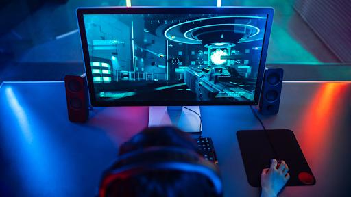 Gamer jogando um FPS em uma mesa com iluminação RGB.