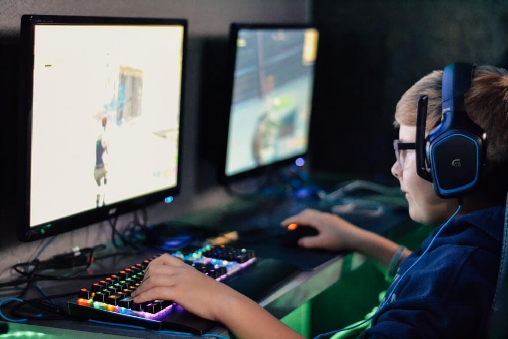 Menino jogando no PC, com acessórios RGB e setup gamer.