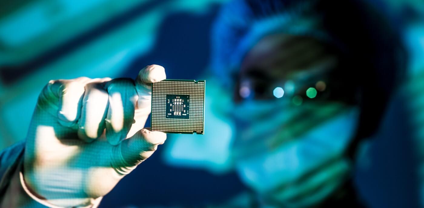 Técnico de laboratório segurando uma CPU (chip).