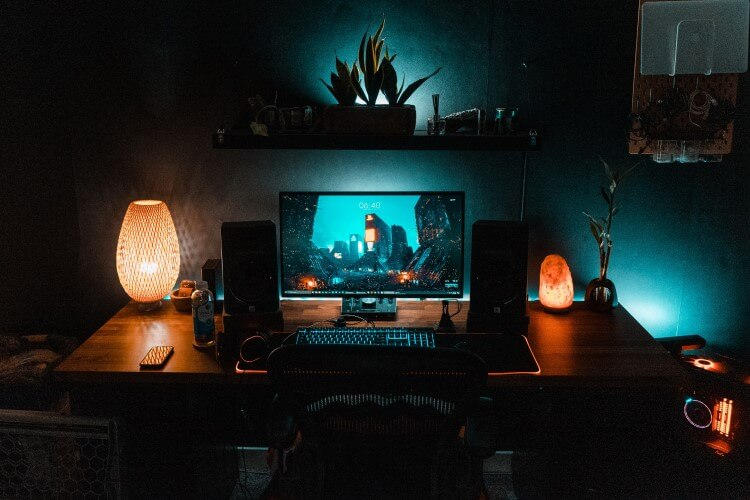 Setup de computador com luminárias sobre a mesa.