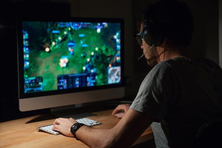 Menino com headset em frente a um computador jogando LOL