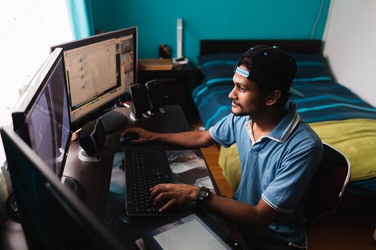 Homem em um quarto mexendo em dois computadores